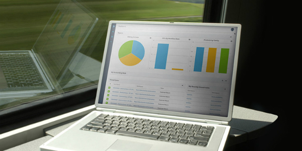 laptop with charts on screen sitting by a window
