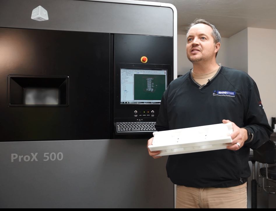 Alan Bradshaw, CEO of Idaho Steel, holds a piston produced six times faster by the ProX 500 SLS printer